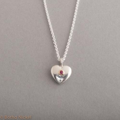 Kette aus Silber mit einem Herzanhänger mit Rubin rund 2,5 mm, Botho Nickel Schmuck Hamburg, Juwelier, Goldschmiede, Gemmologe und Diamantgutachter