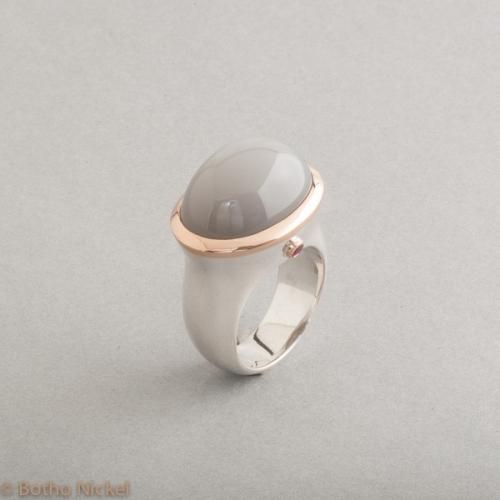 Ring aus Silber mit Mondstein und Rubin, Fassung aus 18 Karat Gold, Botho Nickel Schmuck Hamburg, Juwelier, Goldschmiede, Gemmologe und Diamantgutachter